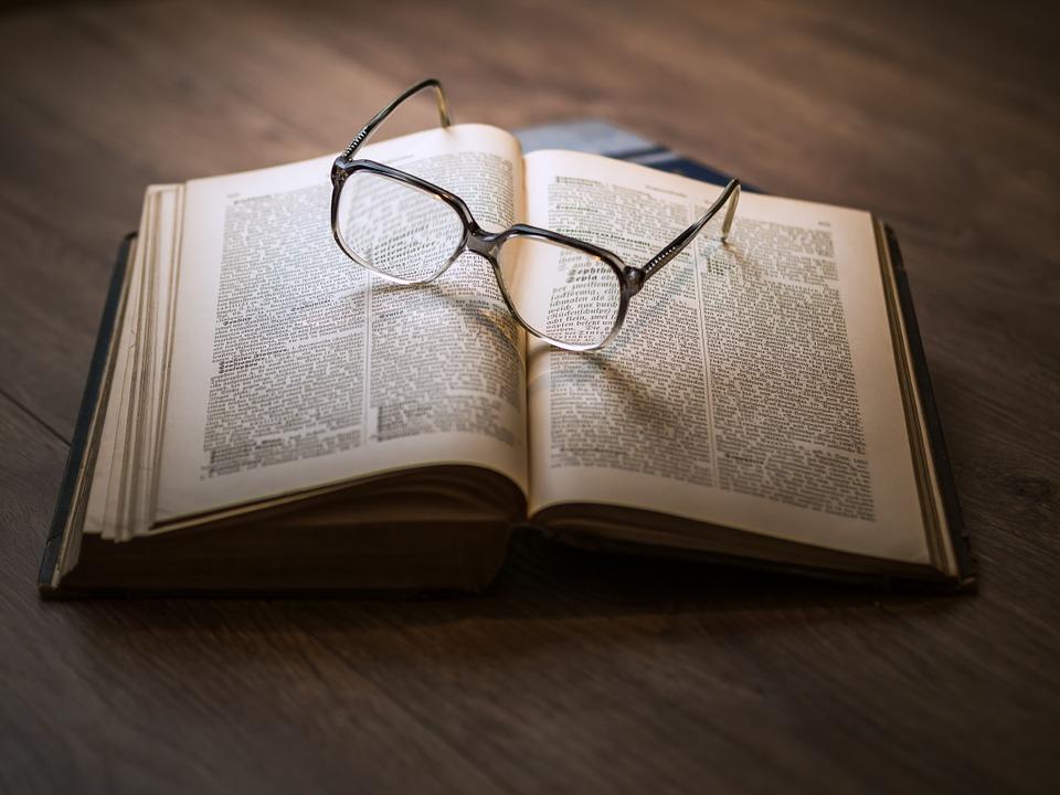 Paire de lunettes loupes posée sur un livre ouvert pour mieux voir