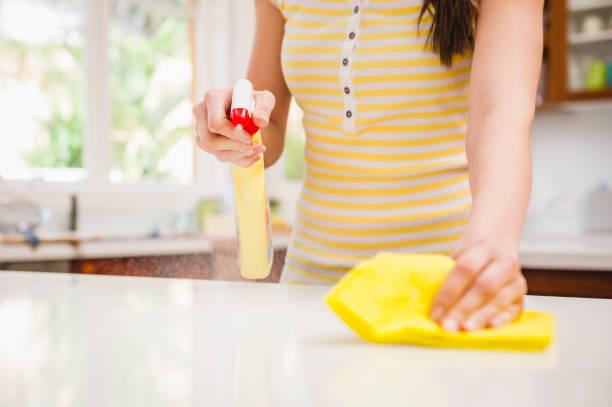 Jeune femme qui fait le ménage dans sa cuisine en désinfectant son plan de travail